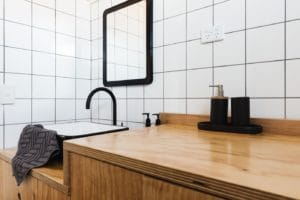 Bathroom vanity made of wood with tiled walls in the background